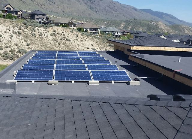 New home construction with solar panels on flat roof
