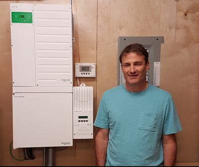 Man standing next to inverter.