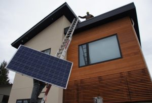 Solar panel being lifted onto Kelowna roof.