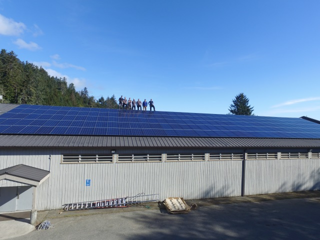 Picture of Terratek team standing on roof filled with solar panels